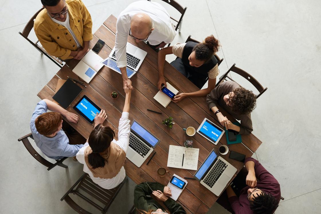 Люди с ноутбуками и другими гаджетами за рабочим столом