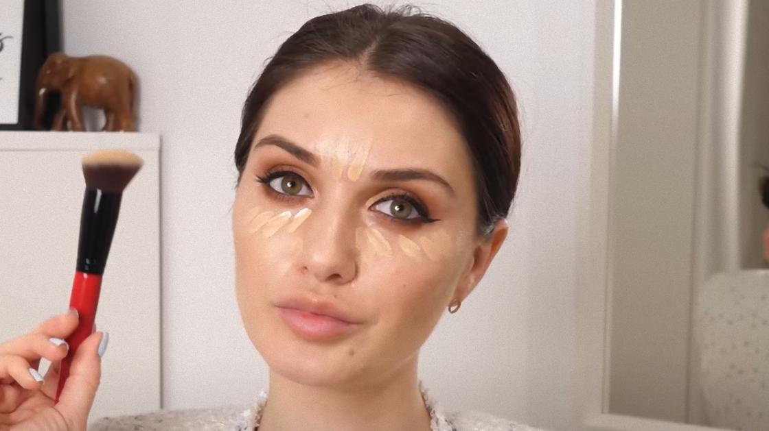 Женщина наносит на лицо тональный крем с помощью кисточки