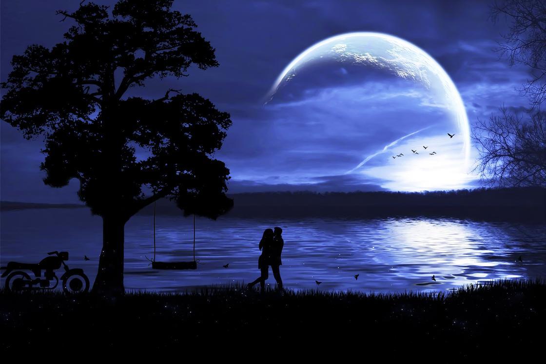 Пара у озера обнимается на фоне полной Луны