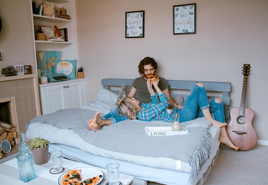 Пара ест пиццу в кровати