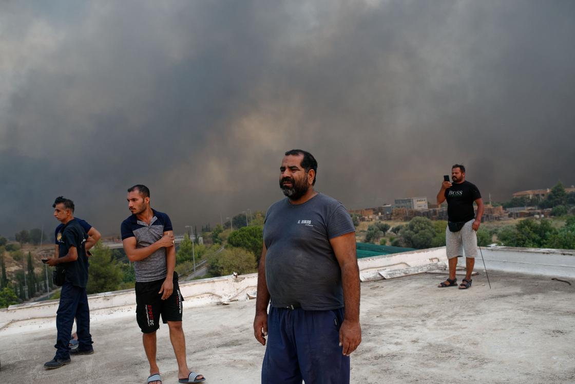 Местные жители наблюдают за тушением пожара недалеко от Афин