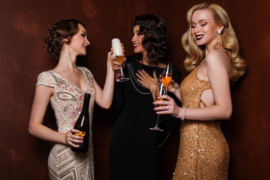 Три девушки пьют шампанское