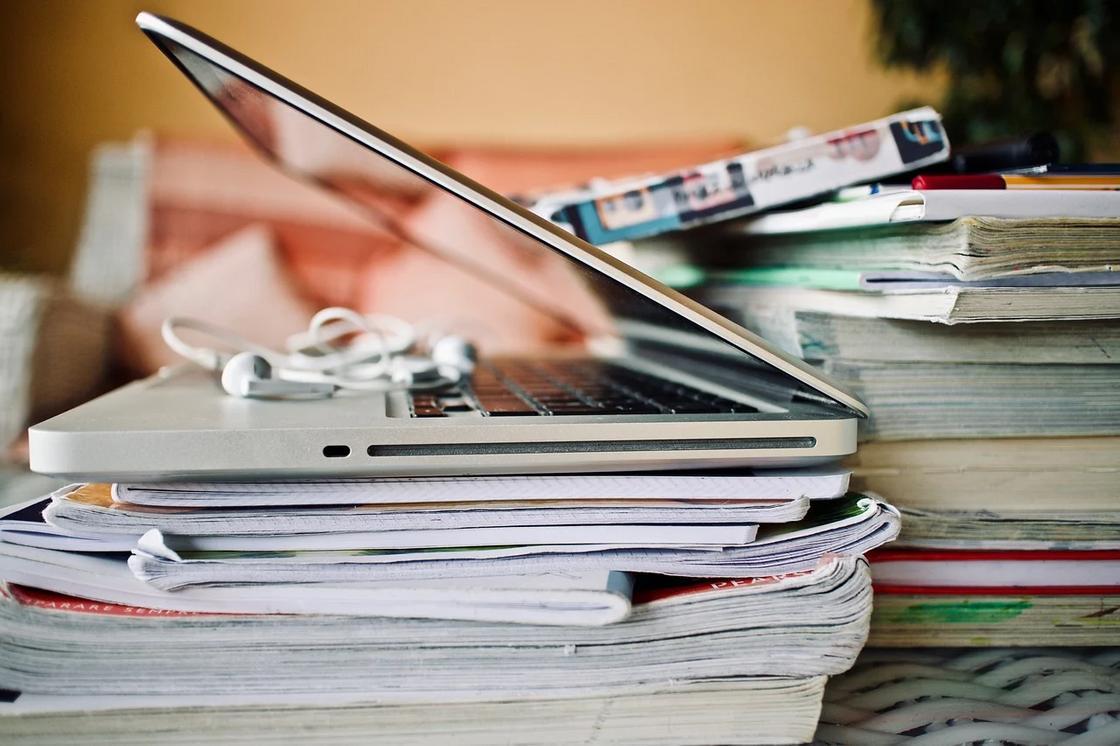 Стопка тетрадей и компьютер на столе