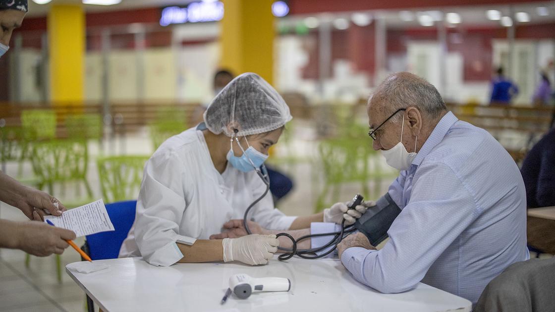Мужчину осматривают перед вакцинацией