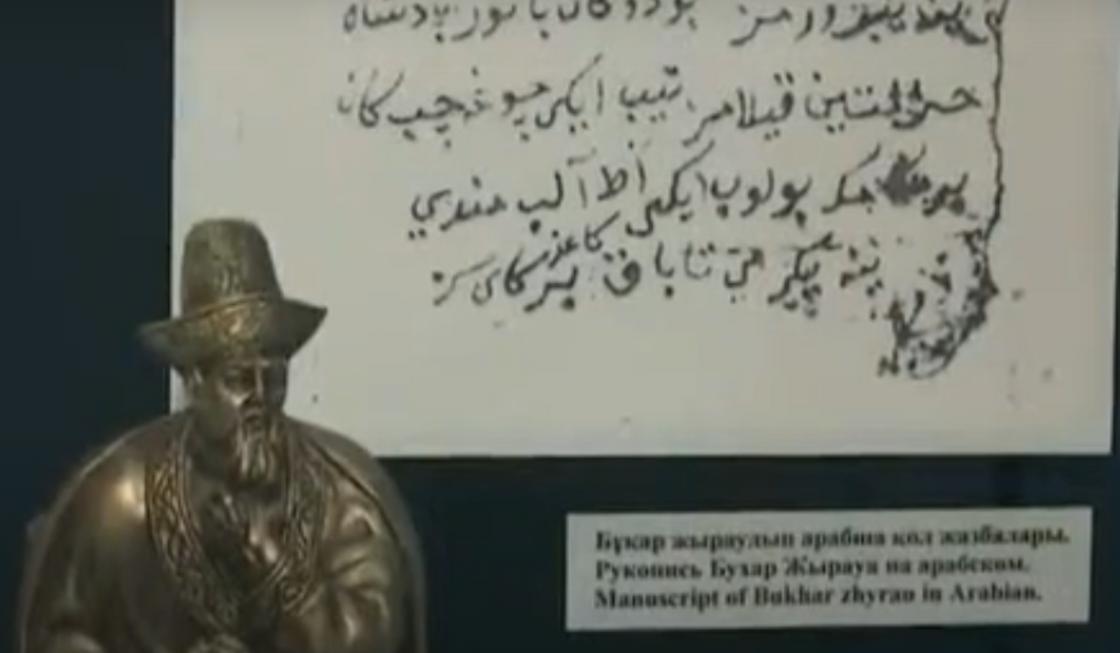 Фигурка акына на фоне текста на арабском