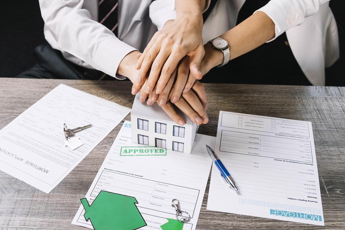 Семейная пара держит руки над договором ипотеки
