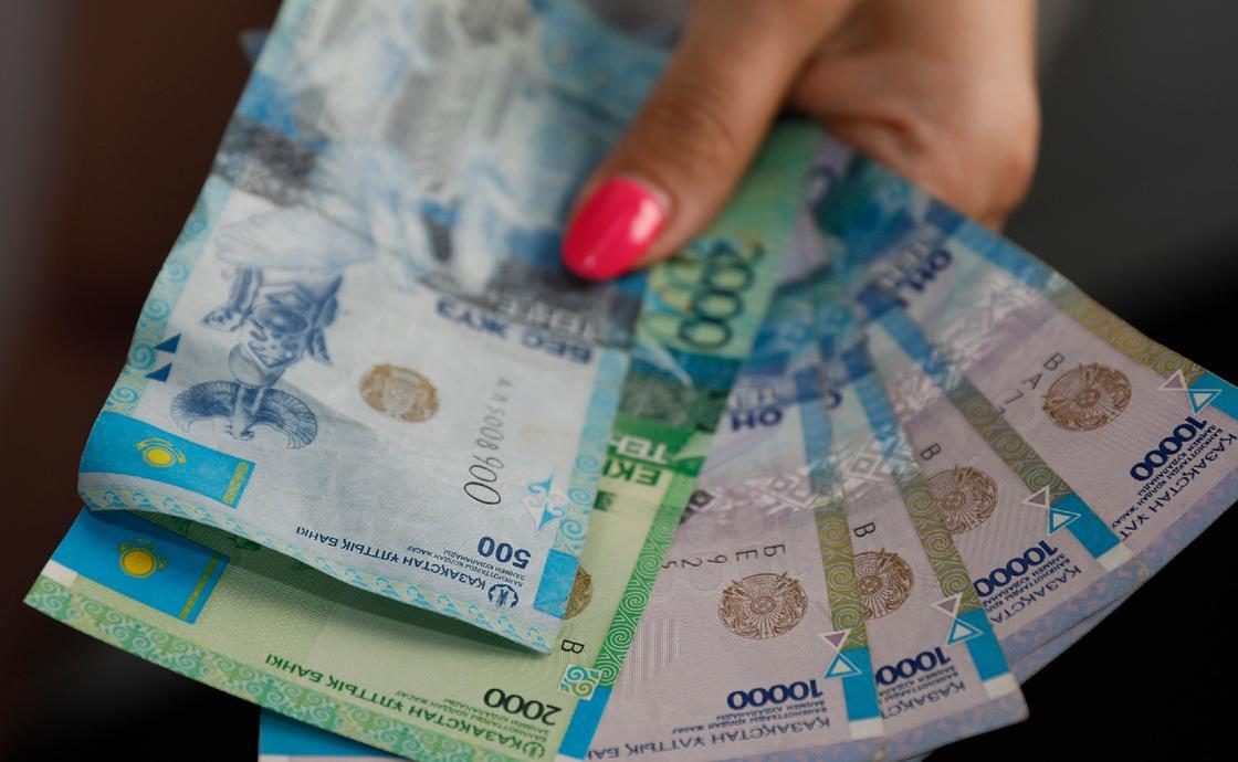 Девушка держит в руках минимальную зарплату