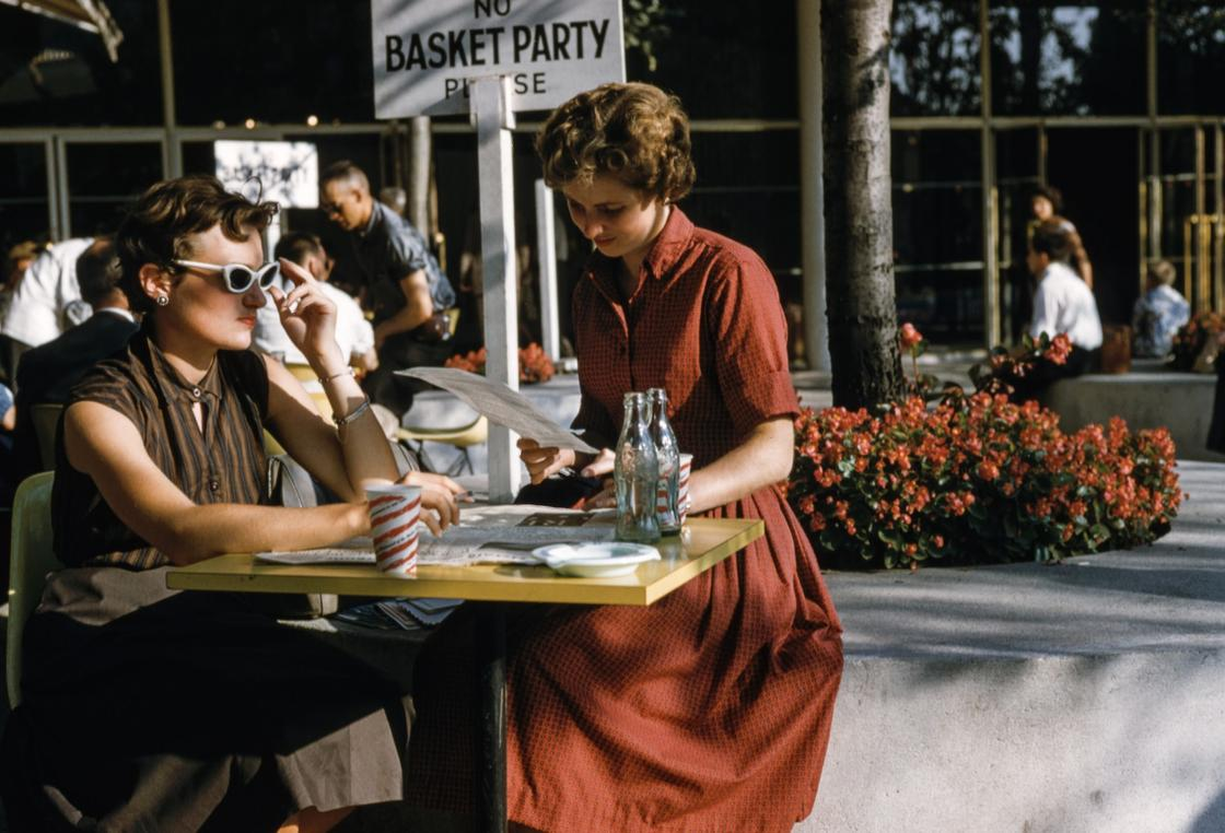 девушка в винтажном платье сидит в кафе