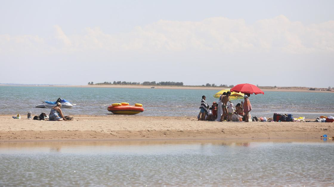 Люди сидят на пляже под зонтом