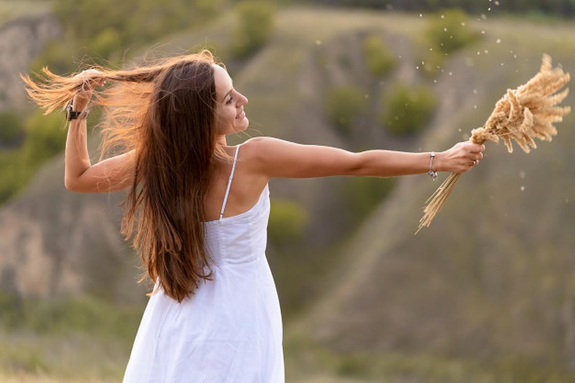 Девушка в белом платье с колосками в руке