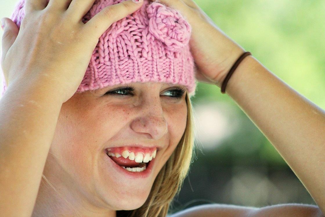 Девушка в шапке смеется