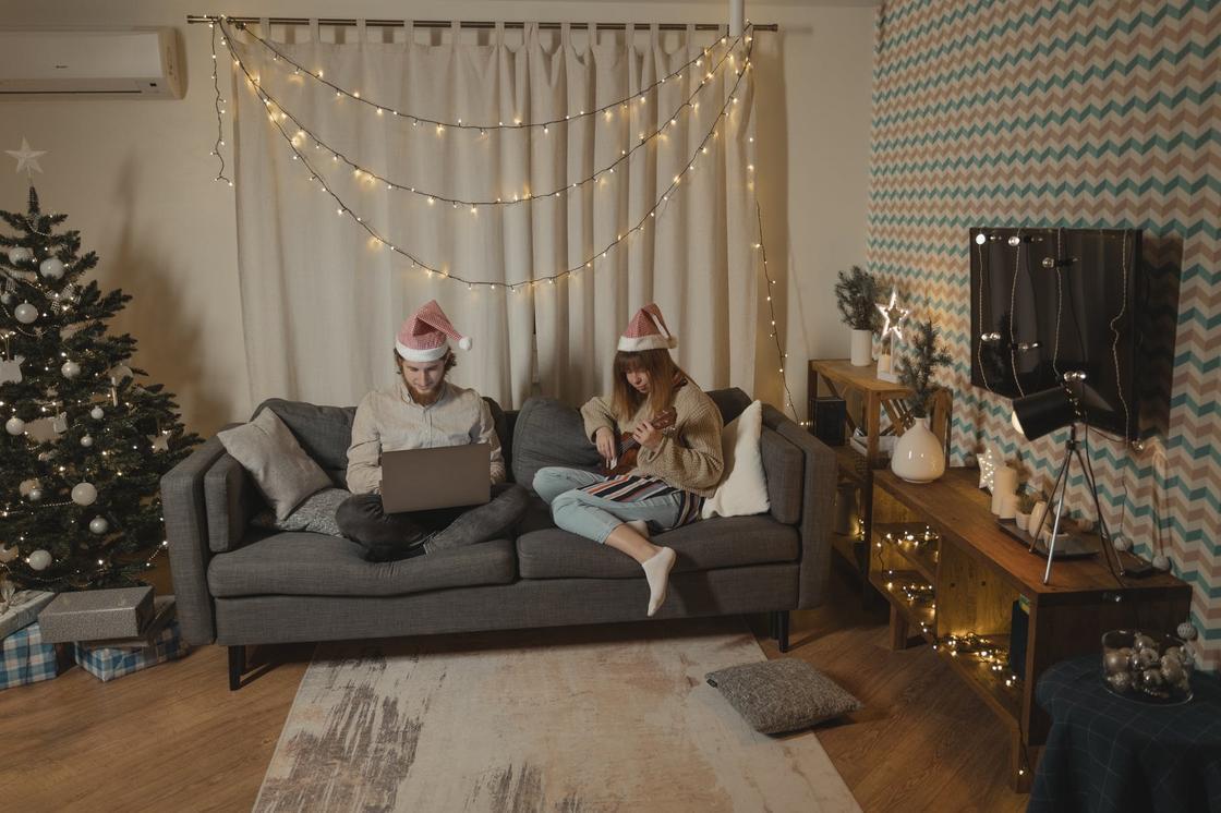 Парень и девушка в украшенной елкой и гирляндами комнате