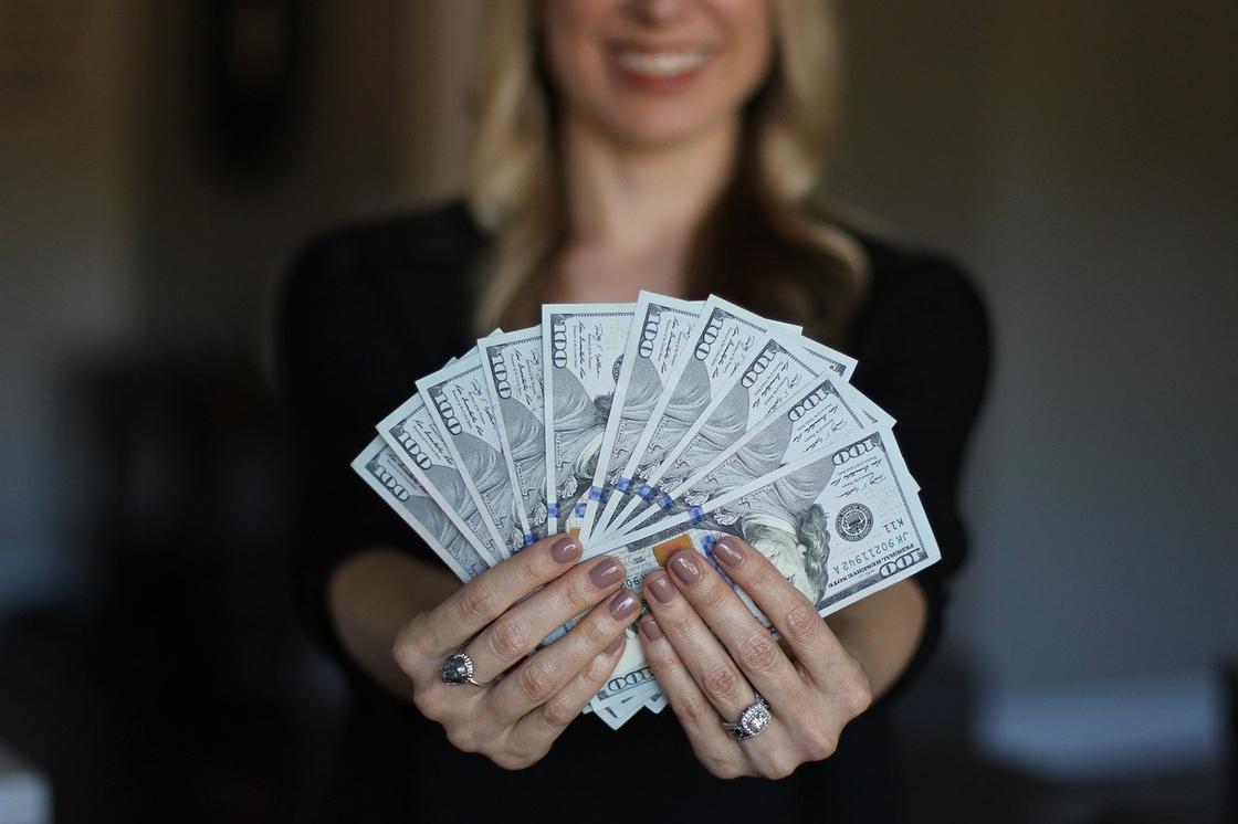 Женщина держит деньги веером