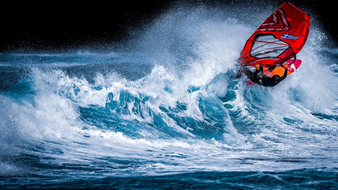 Мужчина, занимающийся виндсерфингом, на гребне волны
