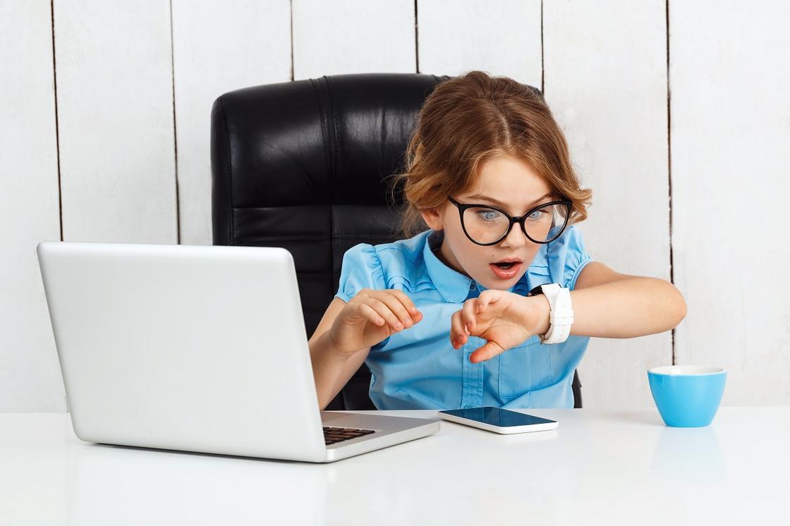 Девочка за рабочим столом смотрит на часы