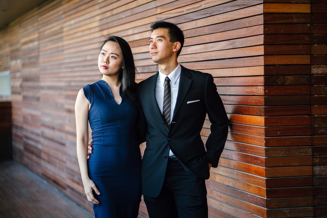 Одетые в деловом стиле парень и девушка стоят на фоне стены