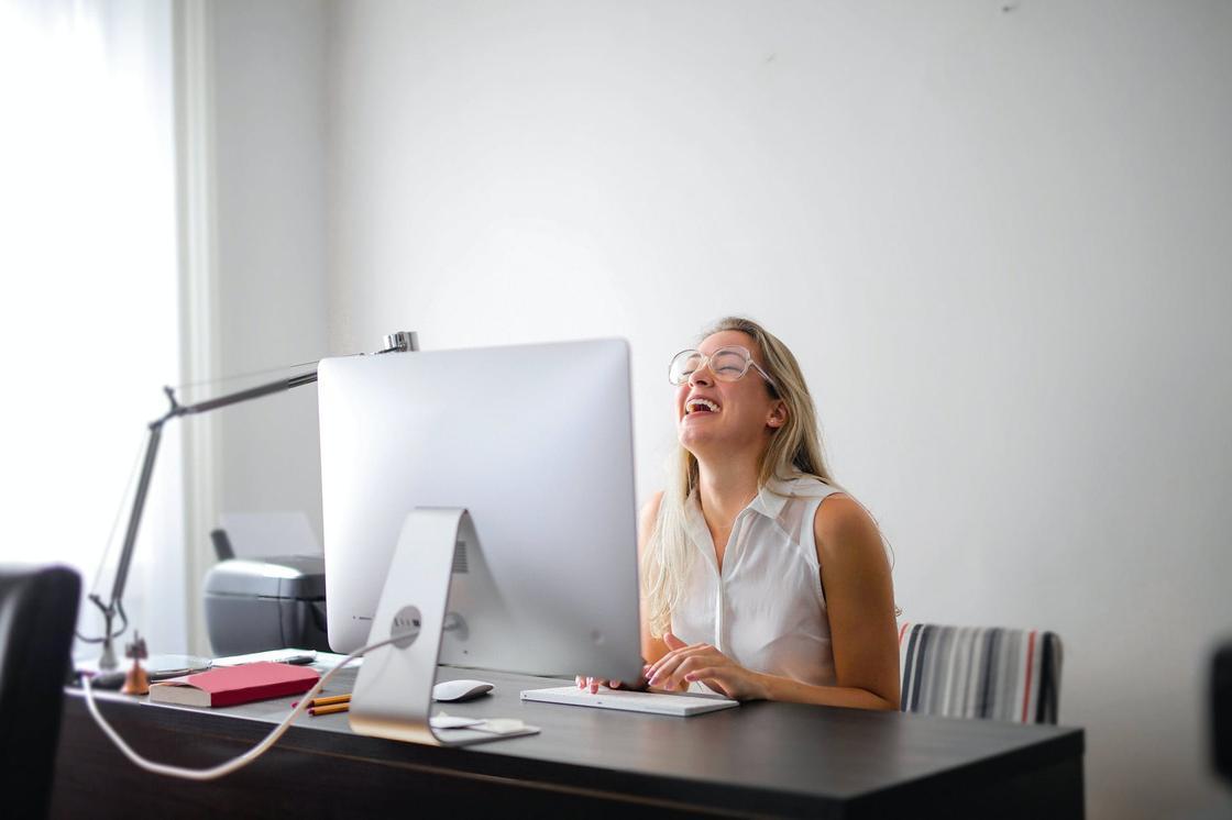Женщина в очках и белой рубашке смеется, сидя за рабочим столом