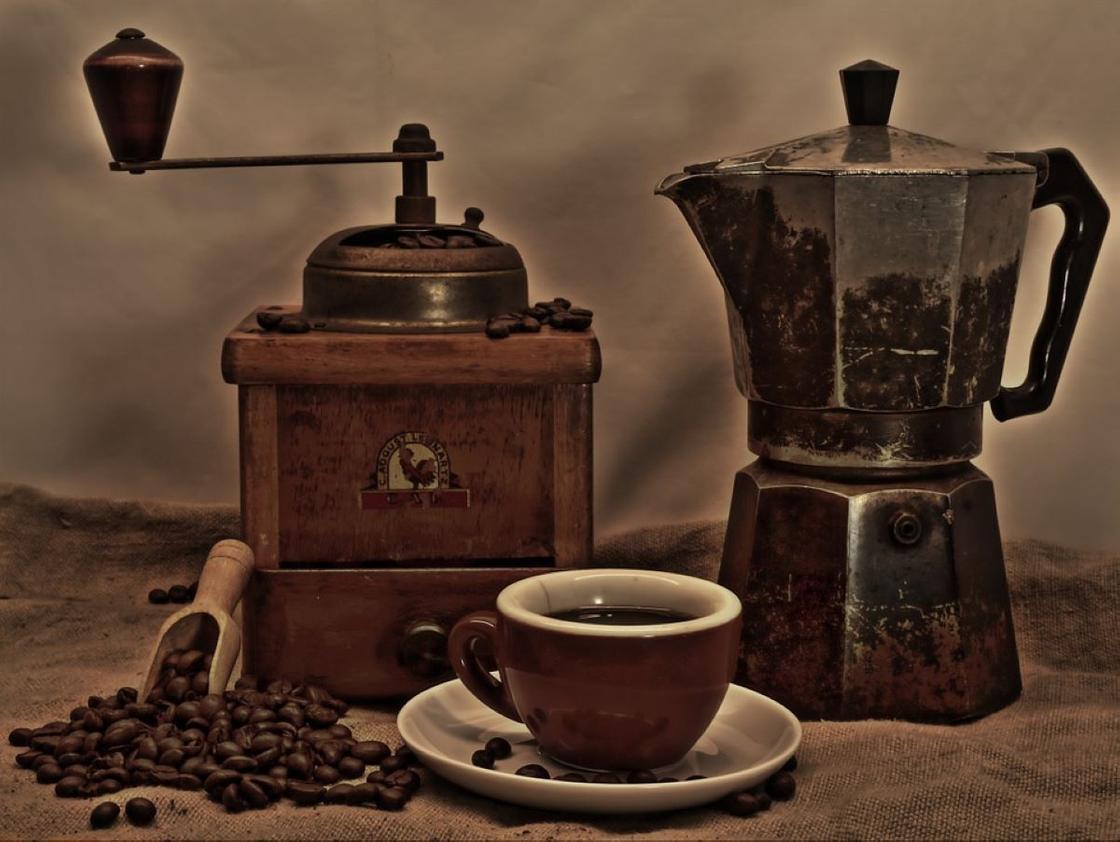 Ручная кофемолка, кофеварка и чашка свежего кофе