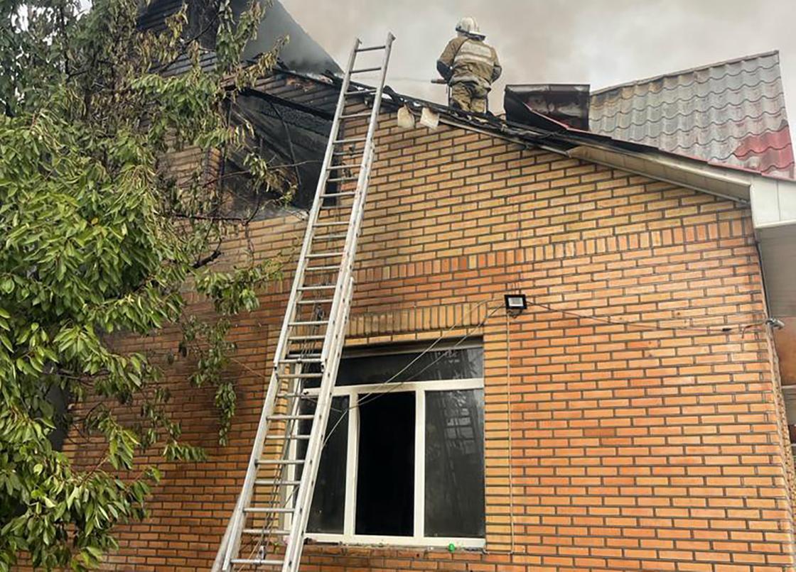 Пожарный забрался по лестнице на крышу дома