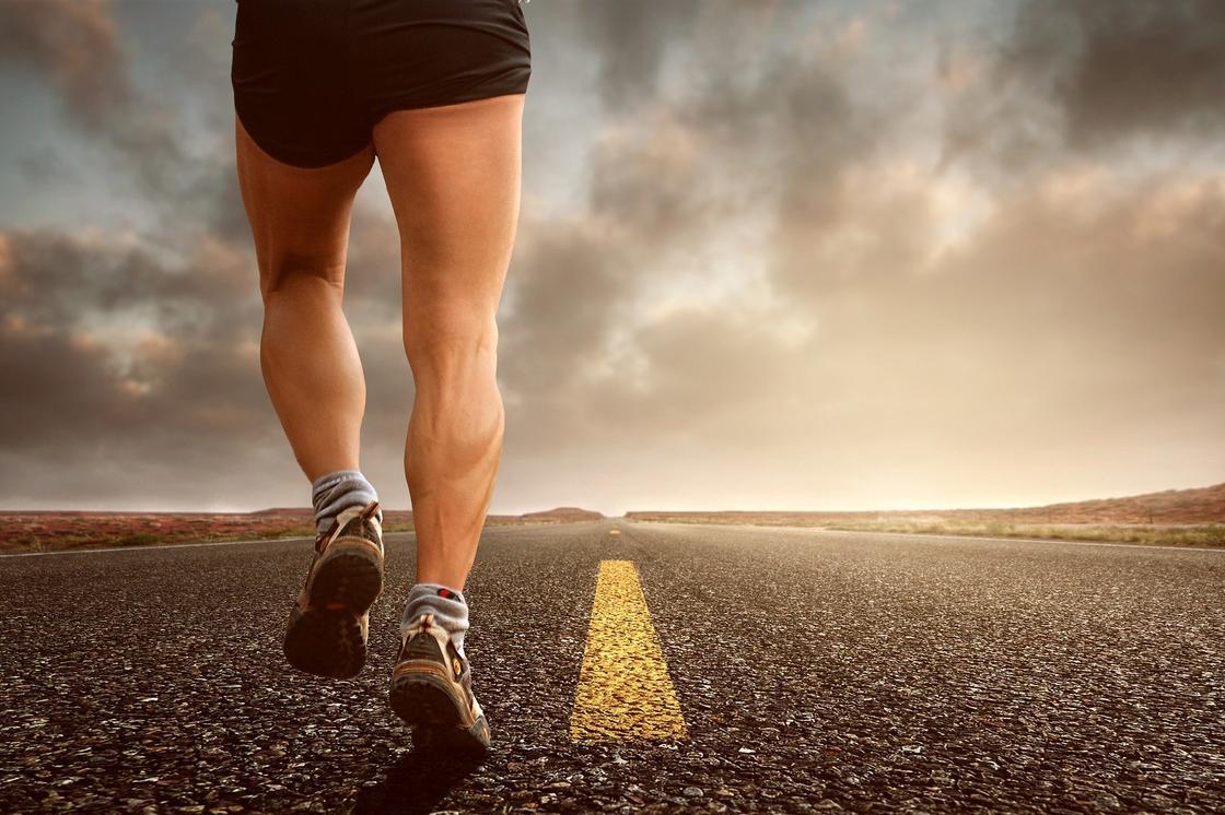 Спортсмен бежит по дороге