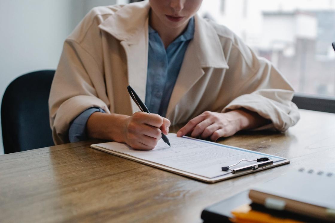Женщина сидит за письменным столом и пишет на листке бумаги