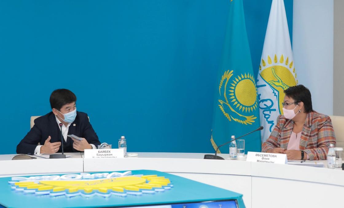 Байбек и Абсеметова сидят за столом в партии Nur Otan