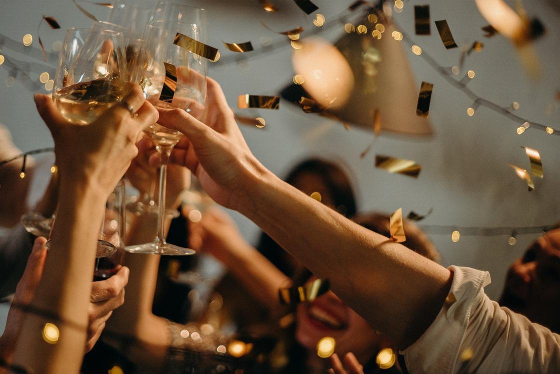 молодые люди чокаются бокалами с шампанским