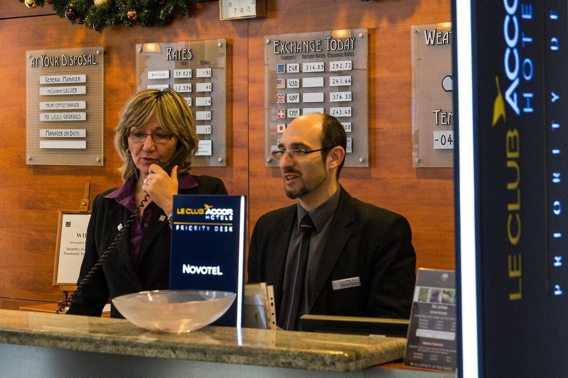 Женщина и мужчина за стойкой регистрации отеля