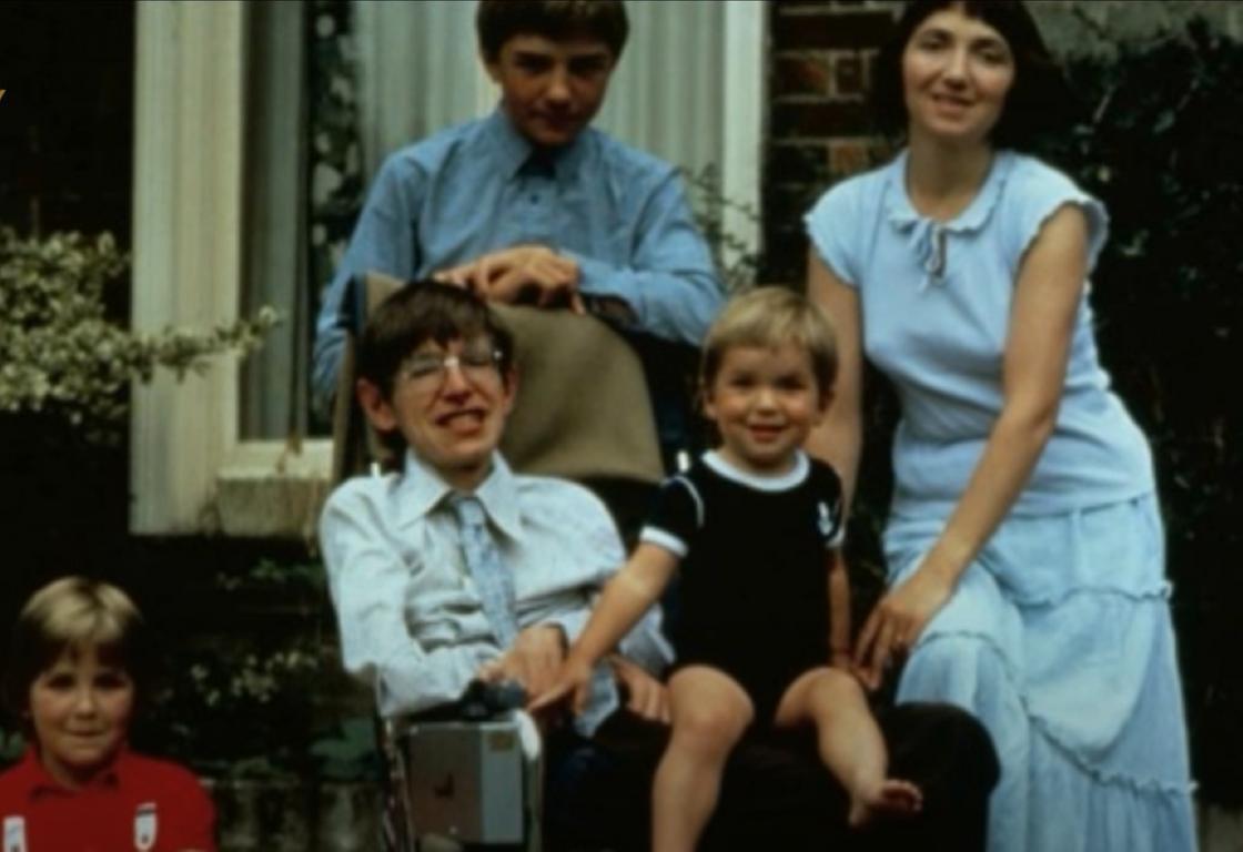 Человек в очках с маленьким мальчиком на коленях, рядом женщина, взрослый мальчик и девочка