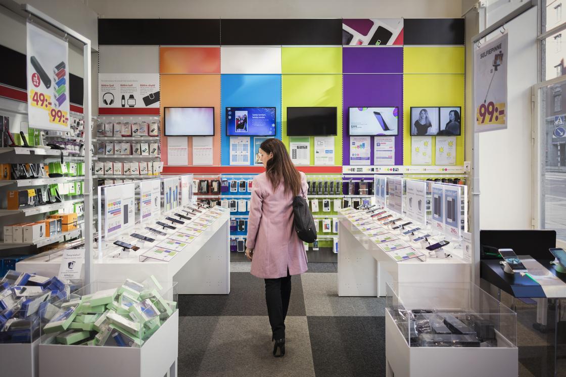 Женщина рассматривает товар в магазине электроники