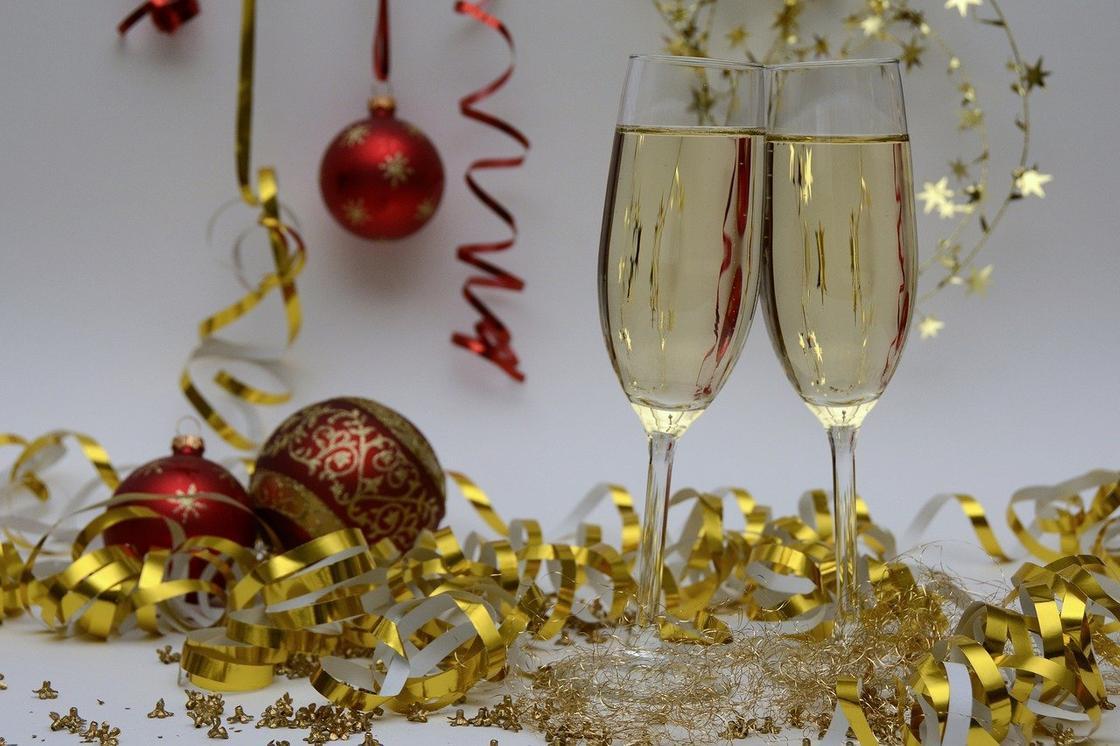 Бокалы с шампанским на фоне новогодней мишуры