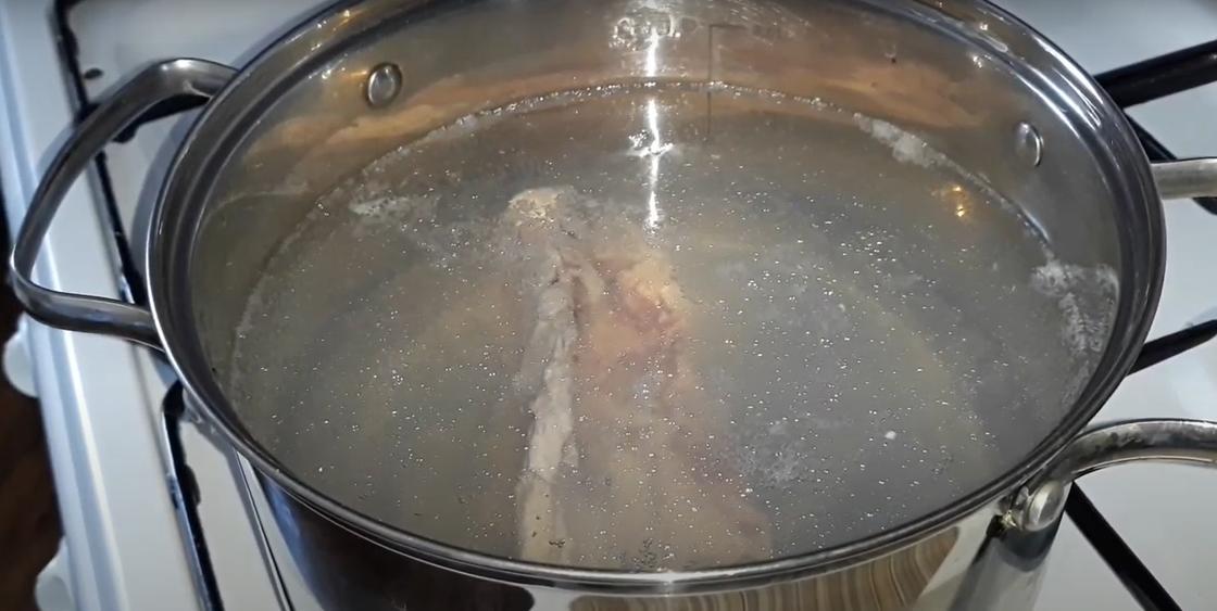 Куриный бульон готовится на плите в кастрюле