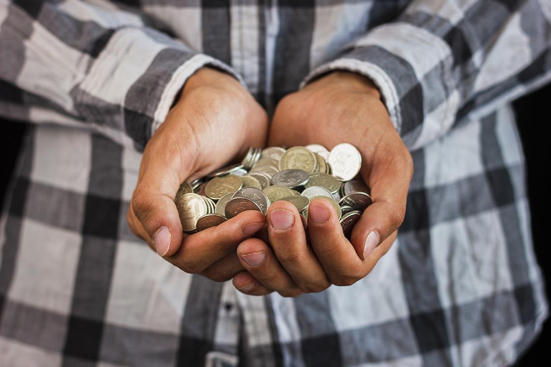 Мужчина держит горсть монет