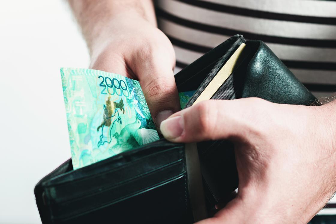 Мужчина держит в руках кошелек с одной купюрой в 2000 тенге