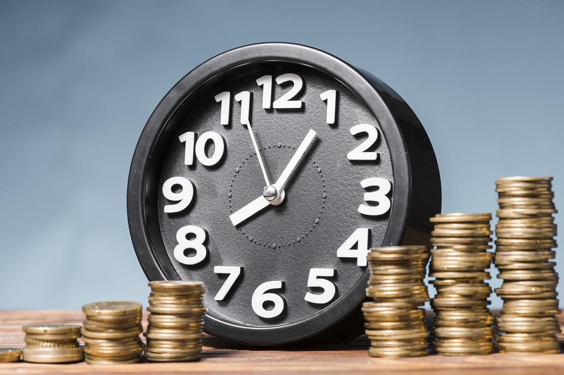 Часы на фоне монет