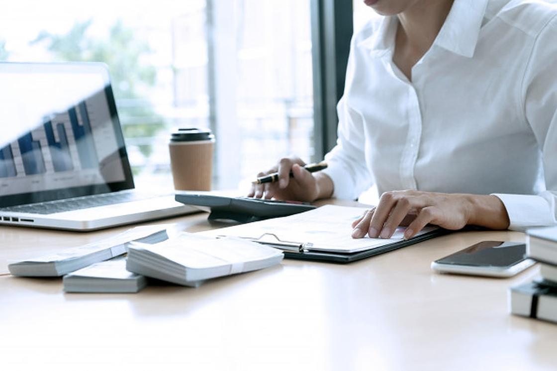 Девушка за рабочим столом с документами