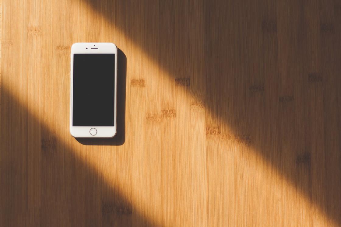 iPhone на деревянной поверхности