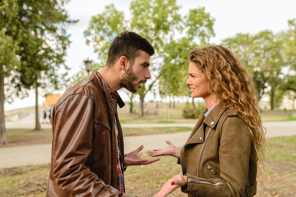 Парень эмоционально разговаривает с девушкой в парке