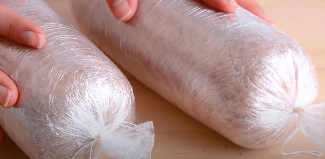 Сырые колбасы, завернутые в пленку