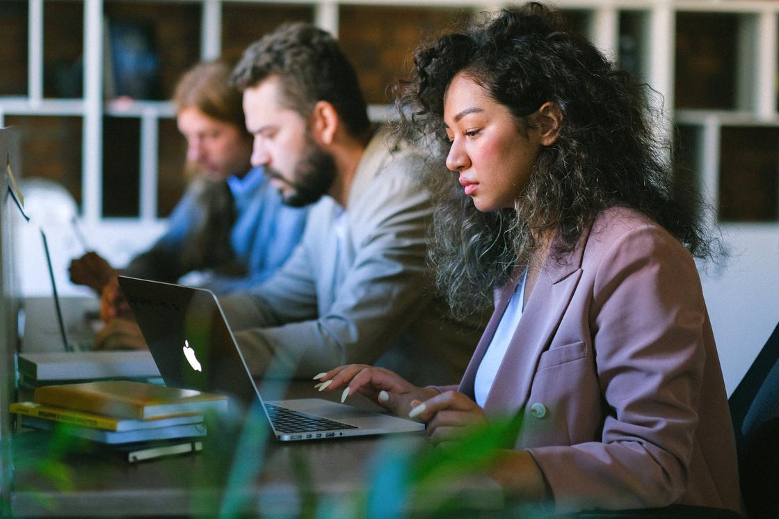 Женщина и двое мужчин, сидящие за компьютерами