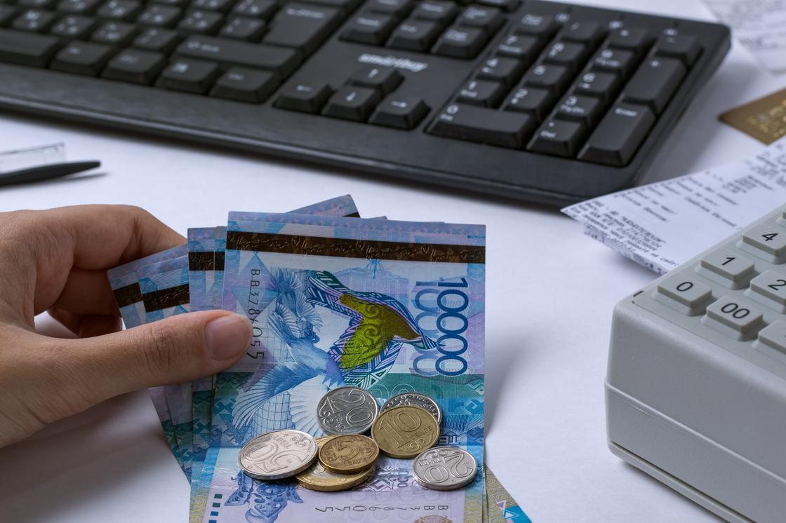 Женщина кладет деньги на стол рядом с кассовым аппаратом