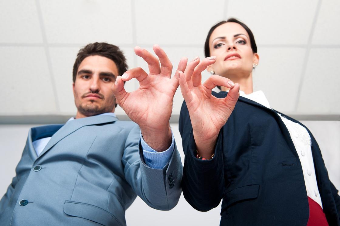 Мужчина и женщина показывают знак «всё отлично»