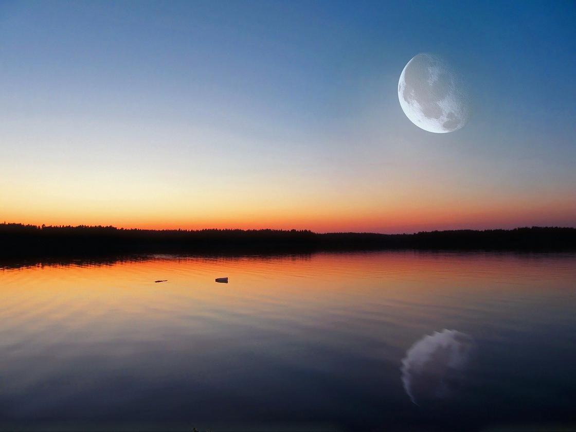 Луна в убывающей фазе отражается в озере