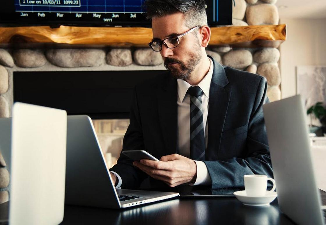 Мужчина в деловом костюме за ноутбуком со смартфоном в руках