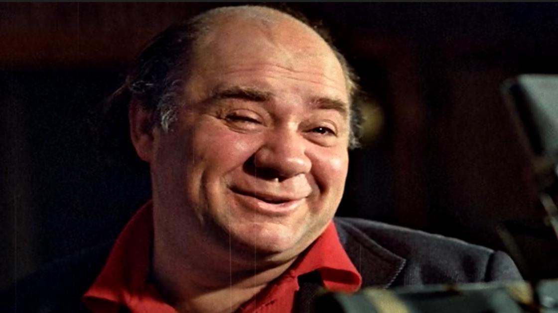 Улыбающийся Евгений Леонов в красной рубашке и пиджаке