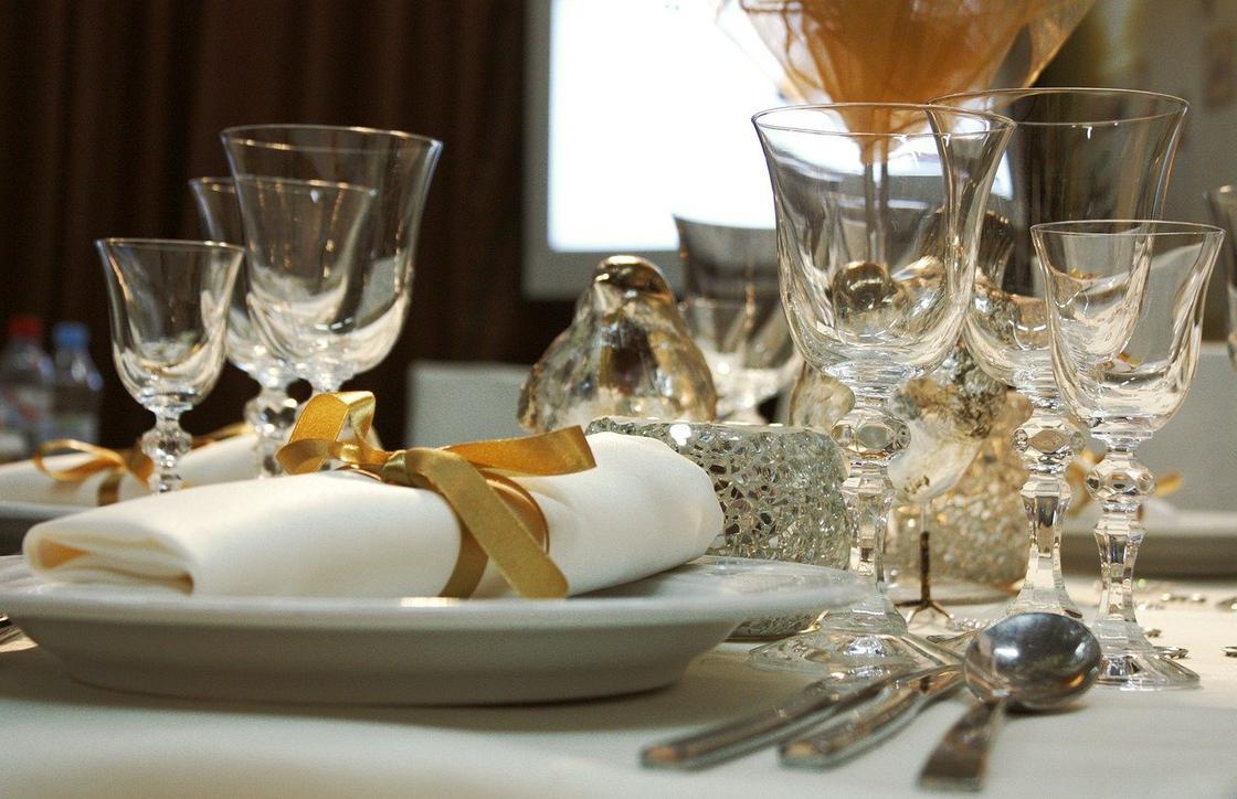 Празднично оформленный стол с рюмками и тарелкамиии