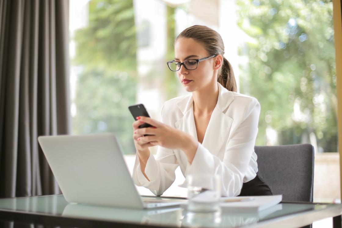 Девушка с телефоном в руках за рабочим столом