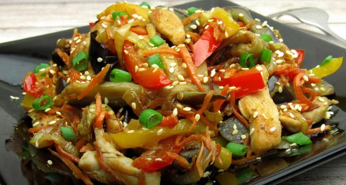 Салат с баклажанами и курицей на тарелке