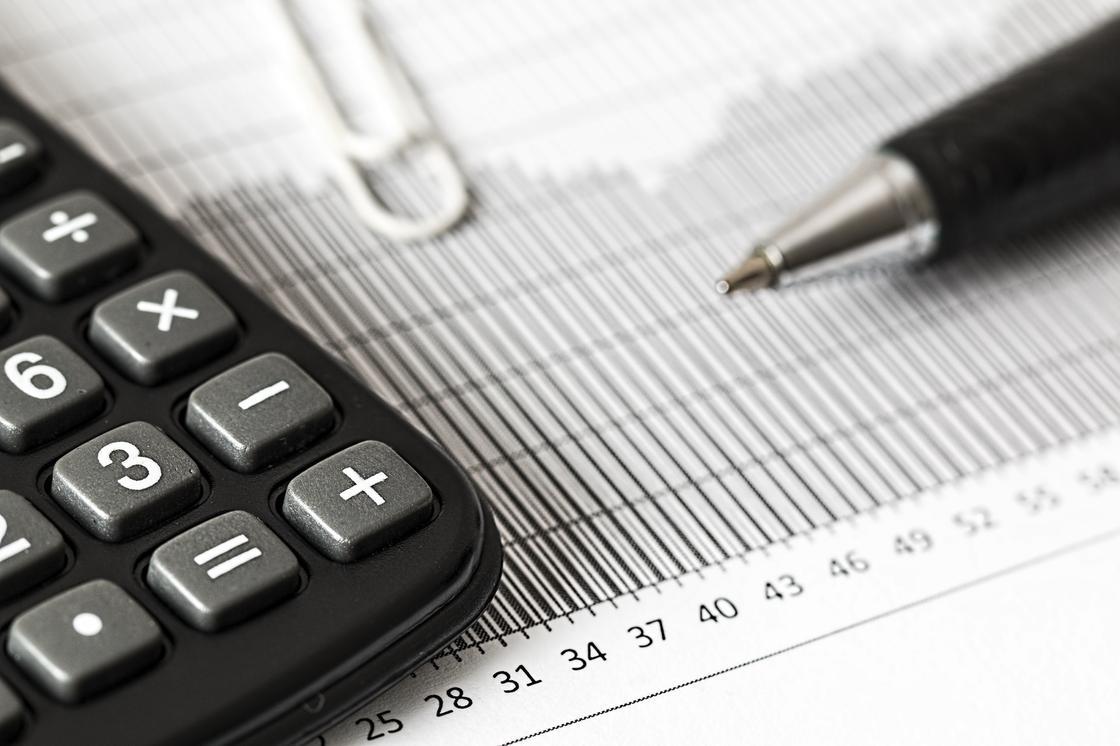Калькулятор и ручка на линованной бумаге