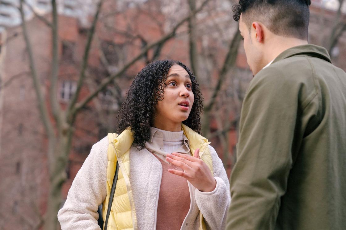 Девушка эмоционально разговаривает с парнем на улице